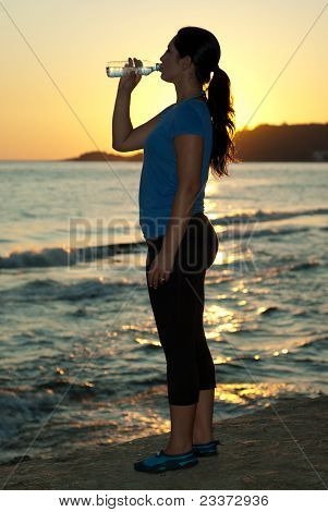Woman Drinking Water By Sunset