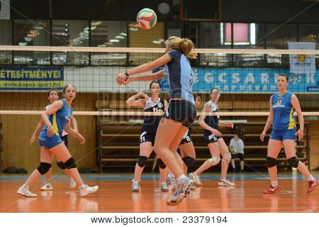 KAPOSVAR, HUNGARY - APRIL 24: Zsofia Horvath (C) receives the ball at the Hungarian NB I. League woman volleyball game Kaposvar (blue) vs Ujbuda (black), April 24, 2011 in Kaposvar, Hungary.