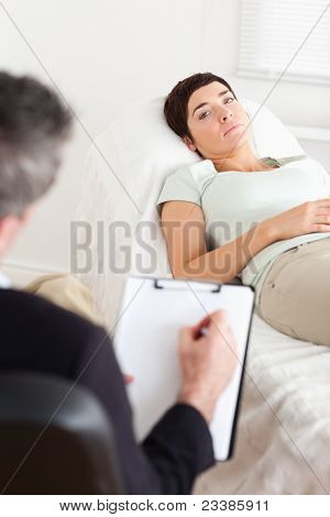 Psychologist talking to a sad female patient in a room