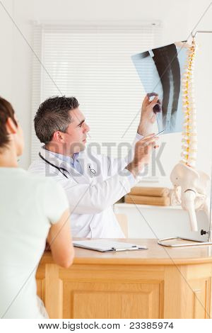 Doctor showing a patient a x-ray in a room