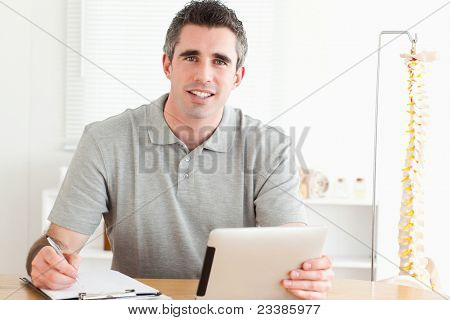 Male Doctor sitting working with a tablet and a chart in a room