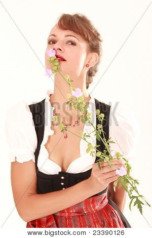 Bavarian woman smelling flower