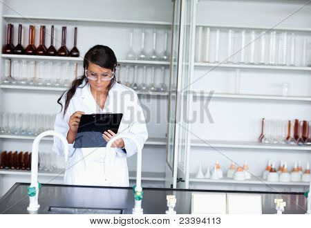 Serious Female Scientist Writing On A Clipboard