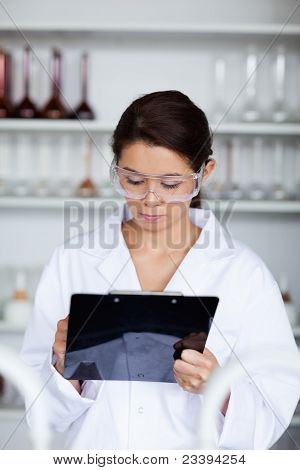 Portrait Of A Scientist Writing On A Clipboard