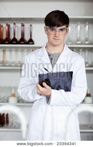 Portrait Of A Male Science Student Writing On A Clipboard