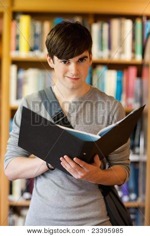 Portrait Of A Smiling Student Holding A Binder