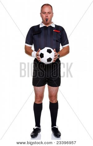 Full length photo of a football or soccer referee holding a ball with a whistle in his mouth, isolated on a white background.