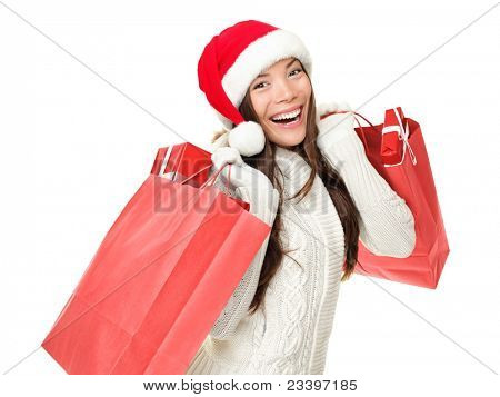 Christmas shopping woman holding shopping bags with gifts. Happy and smiling wearing red santa hat isolated on white background. Mixed race Caucasian / Chinese Asian female model.