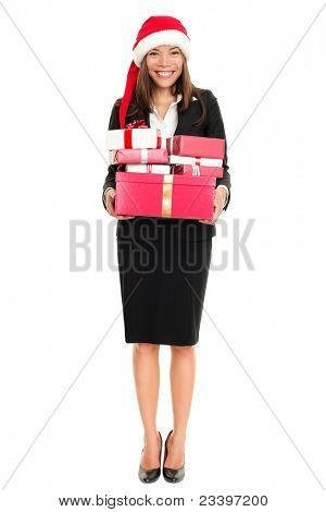 Christmas business woman with santa hat and gifts standing in full length isolated on white background. Happy smiling beautiful multiracial female model.