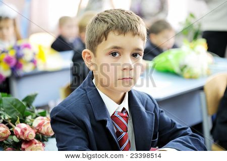 Portrait of first-grader boy sitting at his desk