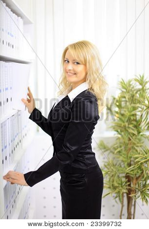 young happy businesswoman near shelf with folders