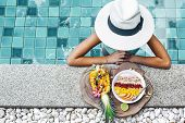 Girl relaxing and eating fruit plate by the hotel pool. Exotic summer diet. Tropical beach lifestyle poster