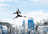 Business Woman Jumping Over Gap With Flying Letters In Concrete Bridge As Symbol Of Overcoming Chall poster