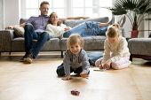 Cute Kids Playing While Parents Relaxing Sofa At Home Together, Smiling Active Boy Entertaining With poster