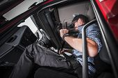 Caucasian Truck Driver Using Seat Belts For His Safety. Heavy Transportation Safety. poster