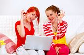 Laughing Girlfriends Using Laptop And Showing Ok Gesture