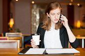 Portrait Of Busy Young Caucasian Businesswoman Drinking Coffee And Talking To Client On Mobile Phone poster