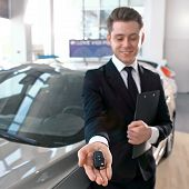 Formal Wearing Young Salesman Offers Brand New Car Key. Close Up Of The Key In The Foreground. Focus poster