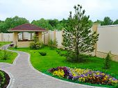Beautiful Landscape Design In A Private Yard. Colorful Flowers, Green Grass And Trees. Cosy Barbeque poster