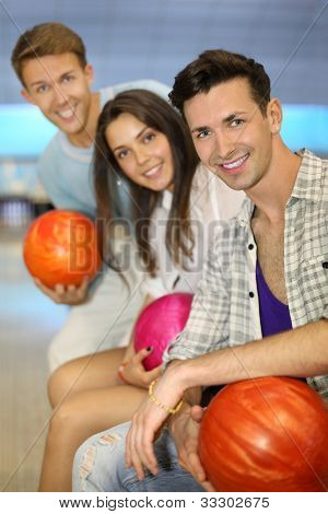 Two beautiful men and woman hold balls in bowling club; shallow depth of field; focus on right man