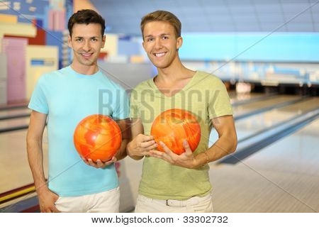 Two young happy men hold orange balls in bowling club; shallow depth of field