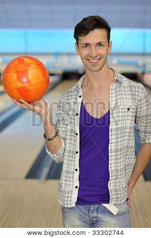 Young smiling man wearing in white checkered shirt holds orange ball in bowling club; shallow depth of field