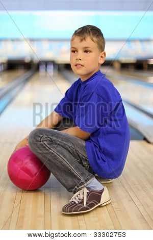 Boy dressed in blue T-shirt with pink ball sits on floor in bowling club; shallow depth of field; full body