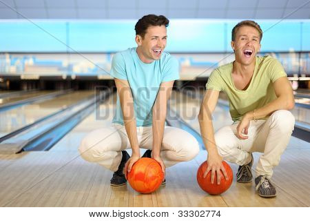 Two laughing men sit on floor with orange balls in bowling club; shallow depth of field; full body