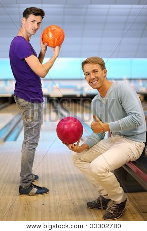 Two young happy men hold balls in bowling club; right man sits and thumb up; left man prepares to throw ball and looks at camera; focus on right man; shallow depth of field