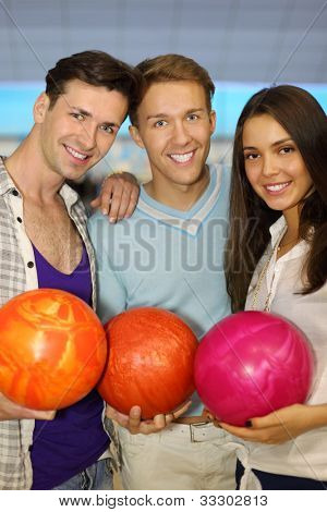 Two young men and beautiful girl hold balls in bowling club; focus on center man; shallow depth of field