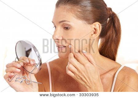 Elderly woman looking for wrinkles around the corner of her mouth in mirror