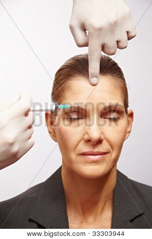 Senior woman getting a syringe injected at plastic surgery