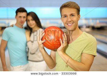 Smiling man holds orange ball; pair stands behind him in bowling club; focus on right man; shallow depth of field
