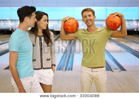 Smiling man shows arm muscles and holds two orange balls; pair look at him in bowling club; focus on right man; shallow depth of field