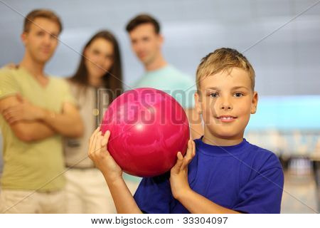 Smiling boy dressed in blue T-shirt holds pink ball in bowling club; two men and woman stand behind him; focus on boy; shallow depth of field