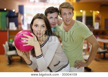 Woman prepares to throw of pink ball in bowling; two men look at aim; focus on woman; shallow depth of field