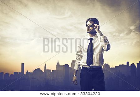 Portrait of a young businessman with skyline of a big city in the background