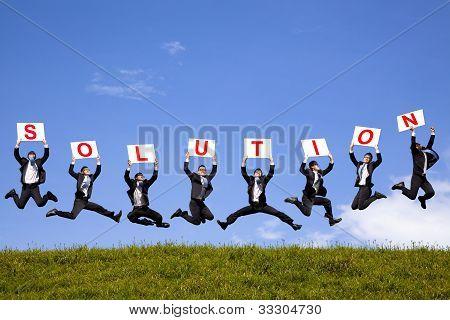 empresario feliz con texto de solución y saltando sobre el campo verde