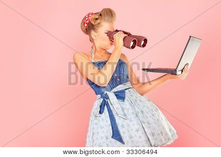 Attractive pin-up girl looking through binoculars to her laptop.