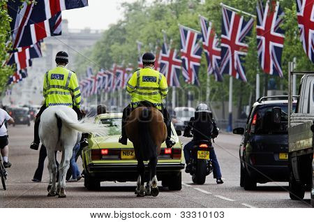 LONDON, UK - APRIL 28, 2011: Mounted policemen on the Mall which is decorated with Union Jack flags in preparation of the Royal Wedding to be held the day after on April 28, 2011 in London.