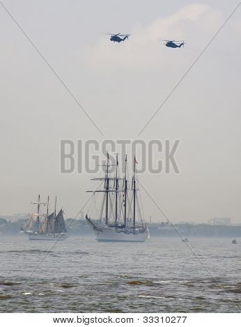 HOBOKEN, NJ - MAY 23: Military helicopters fly above a tall ship along the Hudson River during the Parade of Sails on May 23, 2012 in Hoboken, NJ. The parade marks the beginning of Fleet Week.