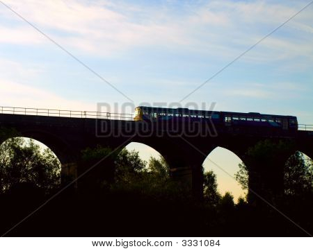Commuter Train On English Viaduct At Dawn
