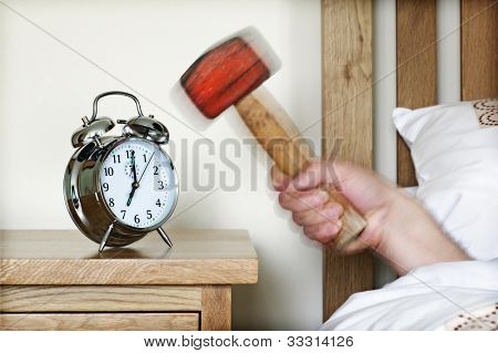 Smashing alarm clock with hammer concept for sleeping in, tired, exhaustion or waking up