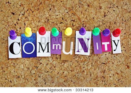 Letras de concepto de comunidad unida a un tablón de anuncios de corcho con chinchetas