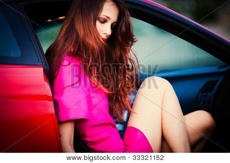 sensual stylish woman in pink dress get out from car