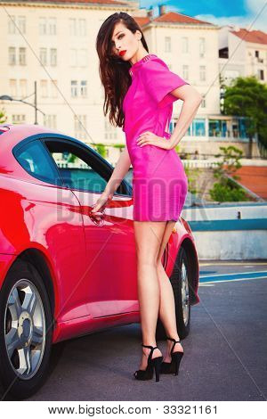 fashion model in pink dress and high heels stand by the red car