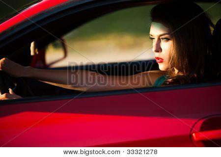 mujer conduciendo coche deportivo rojo, vista lateral, iluminada por el sol