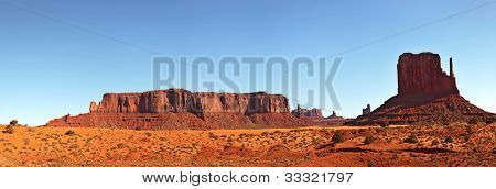 A panorama view of Monument Valley, Utah, USA, against blue sky.