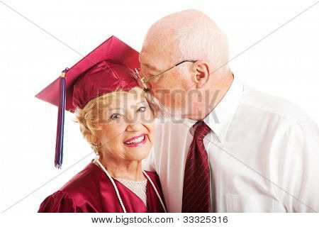 Senior woman earns a college degree and a kiss from her husband.  Isolated on white.
