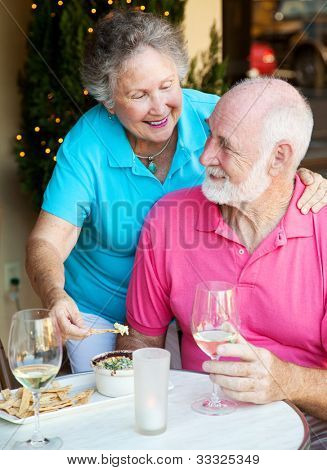 Good looking senior couple enjoying an appetizer and wine at a restaurant.